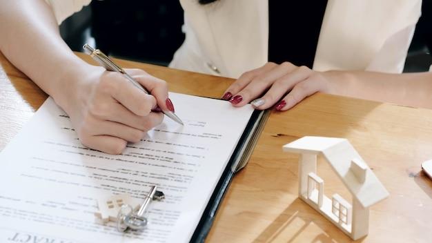 Agenti immobiliari e cliente concordano l'acquisto di una casa e firmano documenti contratto casa con il cliente.