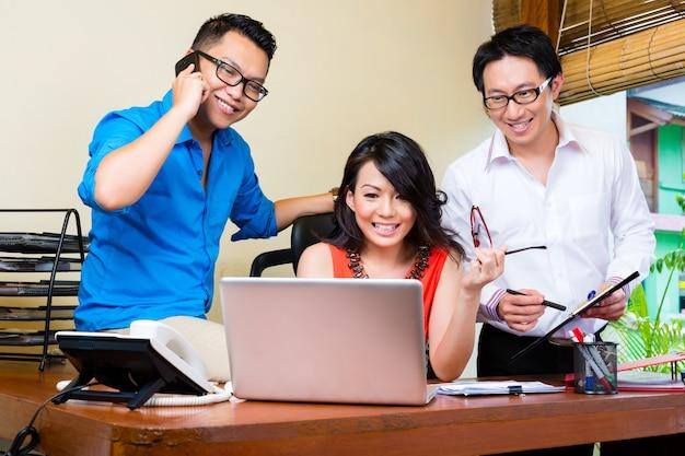 Agenzia creativa asiatica, riunione del gruppo in un ufficio con il computer portatile