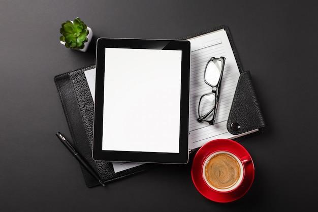 Aggeggio del computer della compressa sullo scrittorio dell'uomo d'affari e sulla tazza di caffè. vista dall'alto con lo spazio della copia