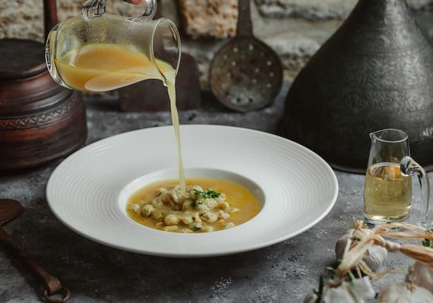 Aggiungendo brodo alla zuppa di pollo con fagioli gialli.