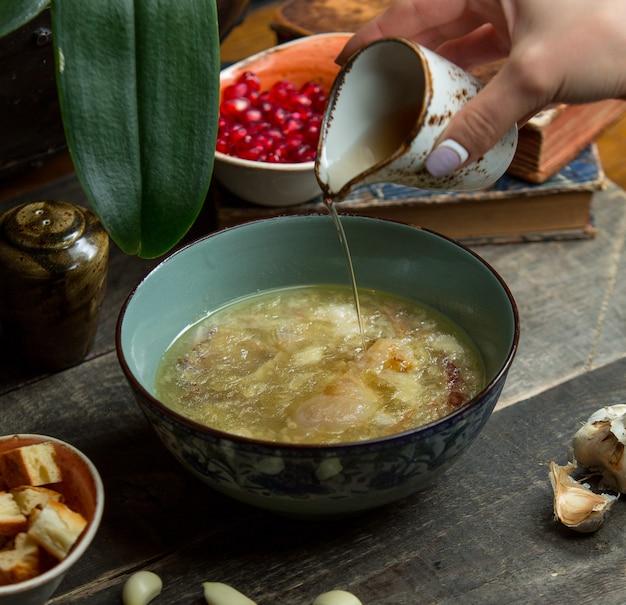 Aggiungendo brodo alla zuppa di pollo in una ciotola autentica blu