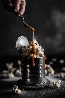 Aggiungendo caramello sopra popcorn salato in una latta d'acciaio su fondo scuro, foto lunatica