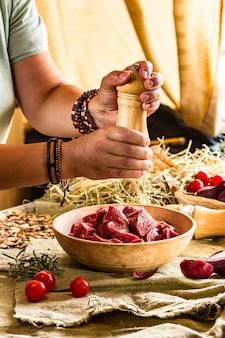 Aggiungi pepe alla carne con un mulino nelle mani dello chef, cornice luminosa. cucina dell'asia orientale. ricetta alimentare, foto, copia del testo