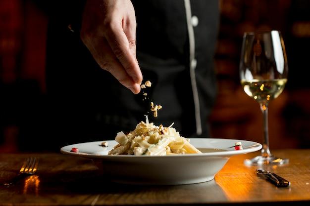 Aggiunta di nocciole alle penne con pollo e spinaci in salsa di parmigiano
