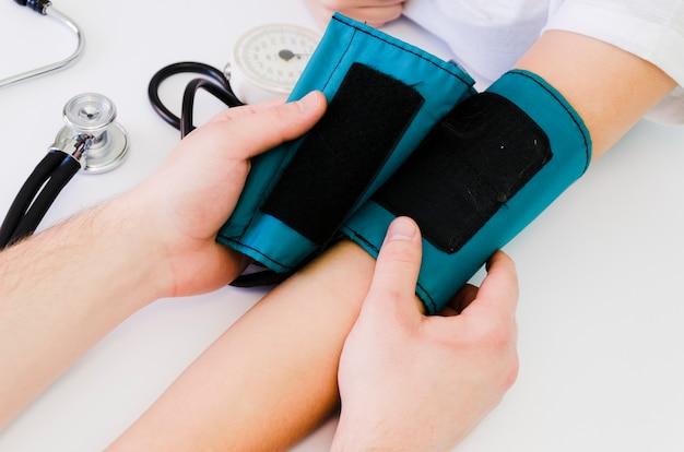 Aggiusti cardiologo che misura pressione sanguigna del paziente sullo scrittorio bianco