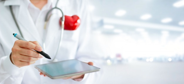 Aggiusti con lo stetoscopio facendo uso della compressa digitale nel concetto dell'ospedale, di sanità e della medicina.
