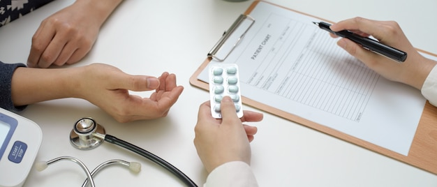 Aggiusti dare le pillole al paziente mentre guardano le informazioni sulla cartella sanitaria