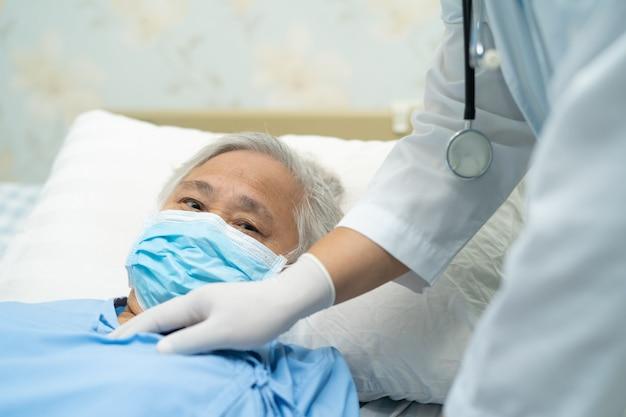 Aggiusti il controllo del paziente asiatico senior della donna che indossa una maschera per proteggere il virus covid-19 di coronavirus.