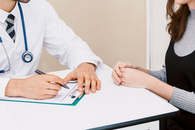 Aggiusti l'informazione medica di controllo con il paziente della donna sulla tavola di medici in ospedale cura e medicina