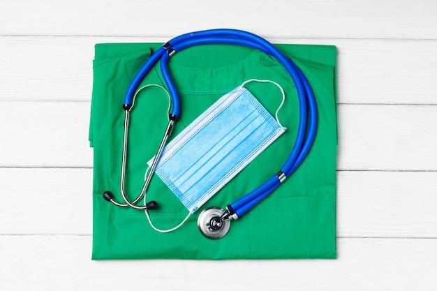 Aggiusti l'uniforme medica con lo stetoscopio e la maschera di protezione su di legno bianco