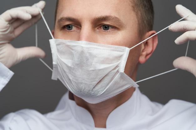 Aggiusti l'uomo che indossa i guanti protettivi del lattice e la maschera di protezione, primo piano