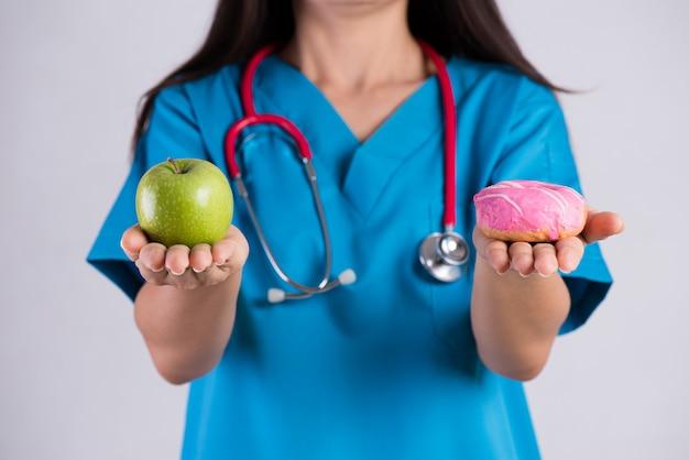 Aggiusti la ciambella della tenuta della mano della donna e la mela verde