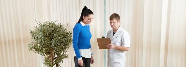 Aggiusti la mostra a paziente femminile i suoi risultati del test medicale in corridoio