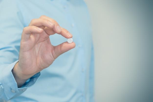 Aggiusti la pillola della tenuta, mano maschio con il farmaco in primo piano della capsula. uomo con tablet, concetto di farmacista, droghe, pillola dimagrante, antibiotici o vitamine