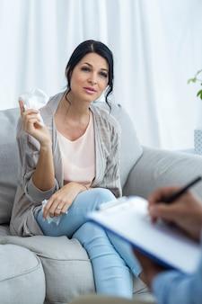 Aggiusti la scrittura sulla lavagna per appunti mentre consultano la donna incinta a casa
