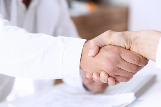 Aggiusti la stretta di mano come ciao con il paziente in ufficio