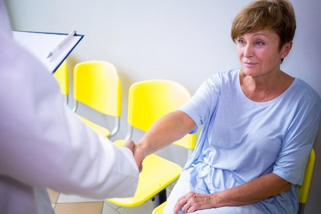 Aggiusti la stretta di mano con il paziente nella sala di attesa