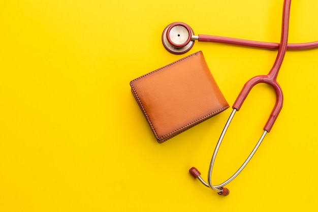 Aggiusti lo stetoscopio e il nuovo portafoglio di cuoio degli uomini marroni su giallo. bilancio per controllo sanitario o denaro e concetto finanziario