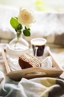 Agglutini con caffè e fiore in vassoio sul letto