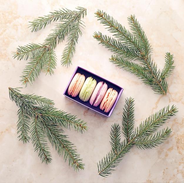 Agglutini i macarons in una scatola viola con i rami di un albero di natale