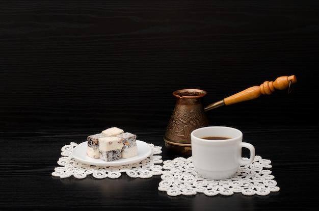 Aggredisca con caffè cezve e delizia turca su fondo nero