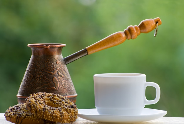 Aggredisca il caffè, i biscotti ed i vasi di rame all'aperto sulla parete verde