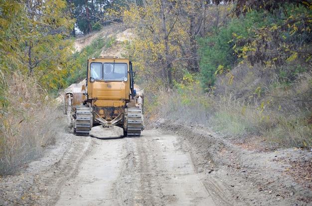 Aggregato di cava con macchinari pesanti. escavatore caterpillar con escavatore a cucchiaia rovescia che conduce alla cava del cantiere
