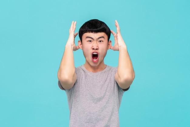 Aggressivo giovane arrabbiato uomo asiatico che grida