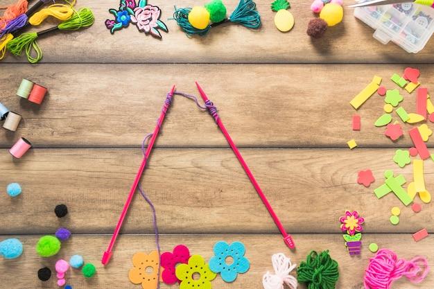 Aghi lavorati a maglia con filo viola all'interno degli elementi decorativi sul tavolo