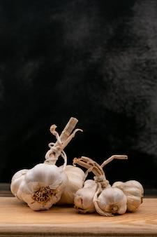 Aglio bianco fresco sul bordo di legno