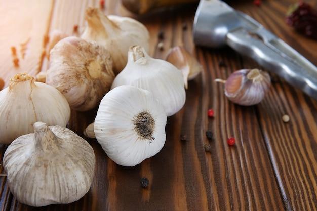 Aglio, spicchi d'aglio e spezie su un tavolo di legno. condimento squisito. sapore naturale antibatterico, aumenta l'immunità. il concetto di cibo biologico sano, medicina alternativa