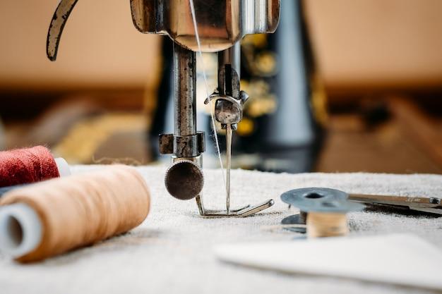 Ago d'acciaio con il crochet e un piedino del vecchio primo piano d'annata della macchina per cucire a mano