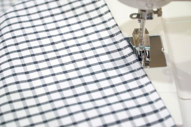 Ago e macchina da cucire con tessuto tartan bianco e nero.