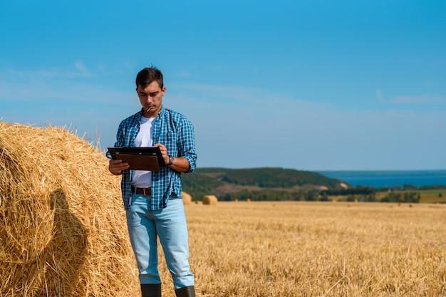 Agricoltore agronomo maschio con un tablet in blue jeans e maglietta bianca e camicia in campo con mucchi di fieno