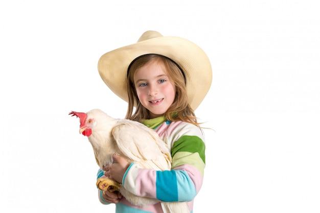 Agricoltore biondo della ragazza del bambino che tiene gallina bianca sulle armi