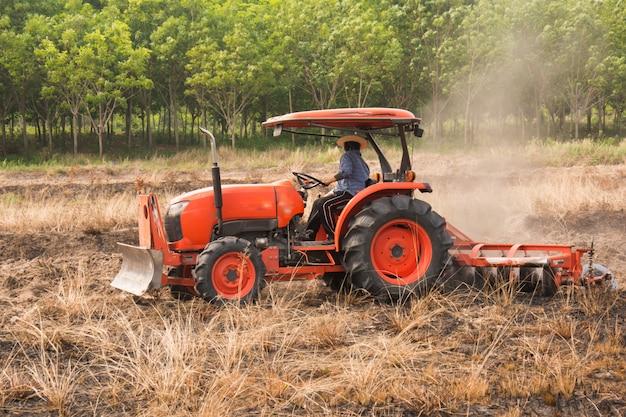 Agricoltore che ara campo di stoppie con trattore arancione