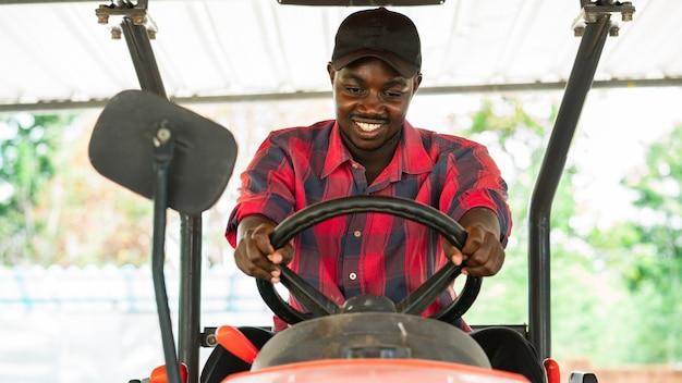 Agricoltore che guida il trattore su un campo dell'azienda agricola