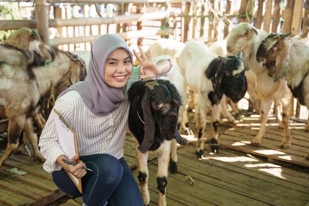 Agricoltore musulmano femminile che fa il controllo per la sua capra nella gabbia