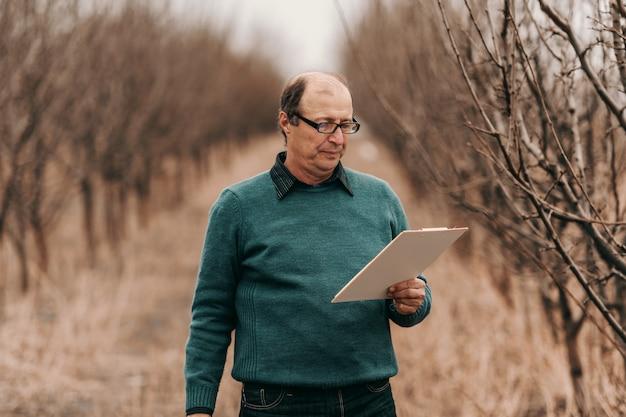 Agronomo calvo caucasico adulto maturo che sta nel frutteto e che esamina lavagna per appunti.