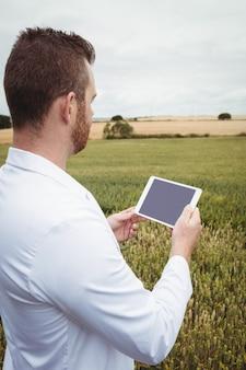 Agronomo che utilizza la tavoletta digitale sul campo