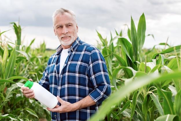 Agronomo invecchiato centrale in un campo che tiene una bottiglia con i fertilizzanti chimici che osservano via