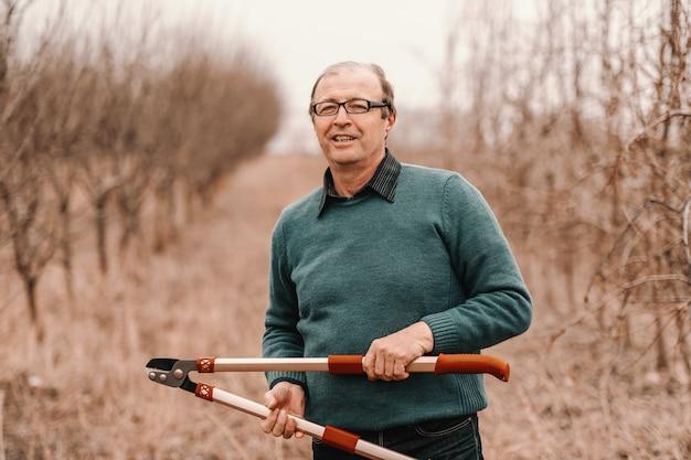 Agronomo senior caucasico con gli occhiali che tengono le forbici della potatura e che stanno nel frutteto.