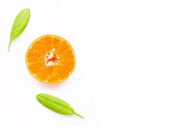 Agrumi arancio freschi con le foglie su fondo bianco.