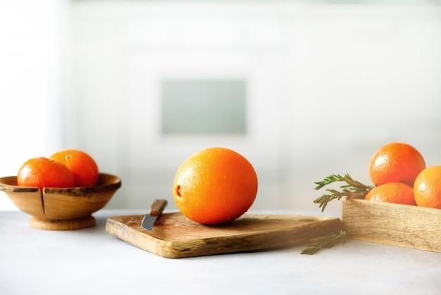Agrumi. frutta fresca, rosmarino grande frutta arancione con gocce d'acqua, coltello, tagliere di legno