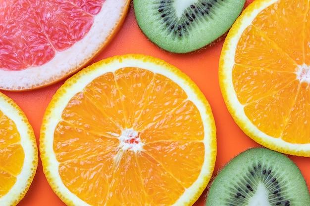 Agrumi, sfondo tropicale. fette di pompelmo, kiwi, arancia.