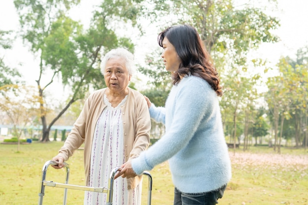 Aiuta e cura il camminatore senior asiatico di uso della donna in parco.
