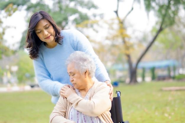 Aiuta e cura la donna senior asiatica che si siede sulla sedia a rotelle in parco.