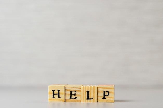 Aiuta la parola fatta di lettere e cubi di legno