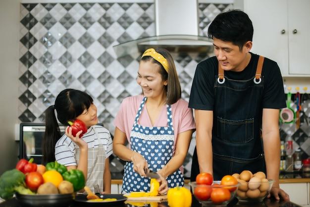 Aiuto sveglio della ragazza i suoi genitori stanno tagliando le verdure e stanno sorridendo mentre cucinano insieme nella cucina