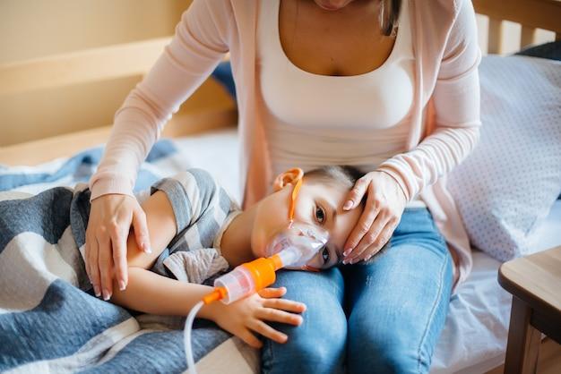 Al bambino viene data un'inalazione da sua madre durante una malattia polmonare. medicina e cura